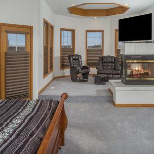 Diseño de dormitorio principal, rústico, grande, con paredes beige, moqueta, chimenea de doble cara y marco de chimenea de baldosas y/o azulejos