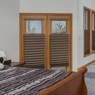 Ejemplo de dormitorio principal, rústico, grande, con paredes beige, moqueta, chimenea de doble cara y marco de chimenea de baldosas y/o azulejos