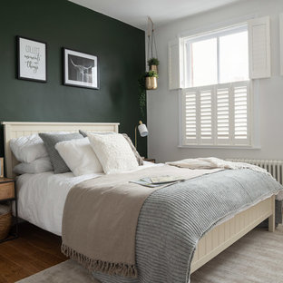 Photo of a mid-sized eclectic master bedroom in Hertfordshire with grey walls, medium hardwood floors and yellow floor.