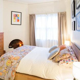 Идея дизайна: спальня среднего размера на антресоли в стиле современная классика с белыми стенами, светлым паркетным полом, угловым камином, фасадом камина из кирпича и белым полом