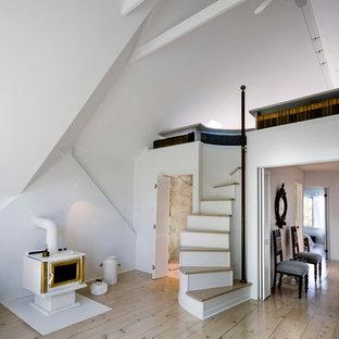 Foto de dormitorio principal, nórdico, grande, con paredes blancas, suelo de madera clara, estufa de leña y marco de chimenea de metal