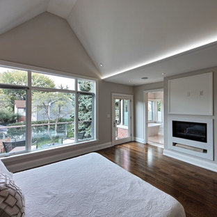 Inspiration for a mid-sized contemporary master bedroom in Toronto with white walls, medium hardwood floors, a ribbon fireplace, a stone fireplace surround and brown floor.