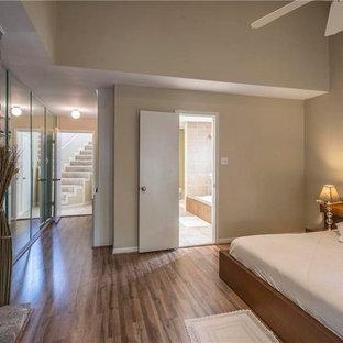 Diseño de habitación de invitados actual, de tamaño medio, con paredes amarillas, moqueta, chimenea de doble cara y marco de chimenea de ladrillo