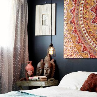 Immagine di una camera da letto bohémian con pareti nere