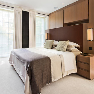 Photo of a contemporary master bedroom in London with carpet, no fireplace and beige floors.