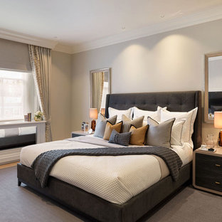 Design ideas for a traditional guest bedroom in London with beige walls, carpet and grey floors.