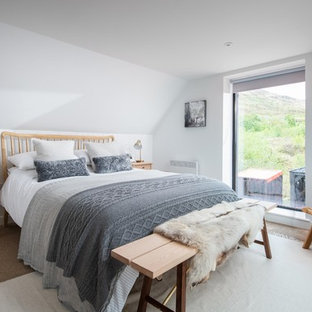 Medium sized scandi master bedroom in Cornwall with white walls, carpet and beige floors.