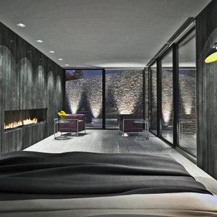 Esempio di una camera matrimoniale minimalista con pareti nere, pavimento in legno verniciato, camino lineare Ribbon, cornice del camino in legno e pavimento bianco