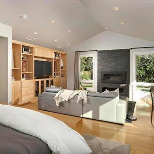 Idéer för stora vintage huvudsovrum, med grå väggar, ljust trägolv, en bred öppen spis och beiget golv