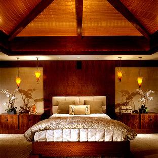 Imagen de dormitorio principal, tropical, grande, con paredes beige, moqueta, chimenea tradicional y marco de chimenea de piedra