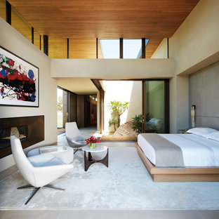 Idée de décoration pour une grand chambre parentale minimaliste avec un mur beige, un sol en calcaire, un sol beige, une cheminée ribbon et un manteau de cheminée en métal.
