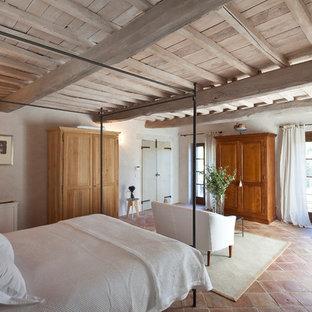 Стильный дизайн: спальня в средиземноморском стиле с бежевыми стенами, полом из терракотовой плитки и красным полом - последний тренд