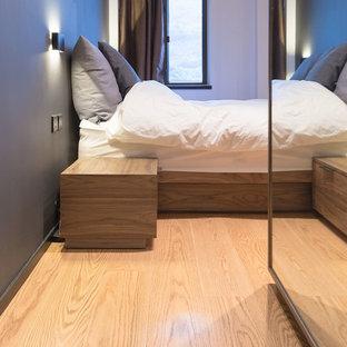 Ejemplo de dormitorio principal, industrial, pequeño, sin chimenea, con paredes grises y suelo de contrachapado