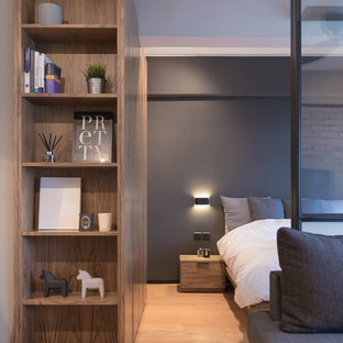 This is an example of a small industrial master bedroom in Hong Kong with grey walls and plywood floors.