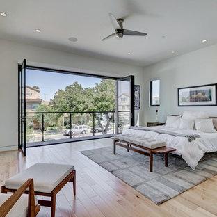 Foto de dormitorio principal, actual, con paredes grises, suelo de madera clara, chimenea lineal, marco de chimenea de hormigón y suelo beige