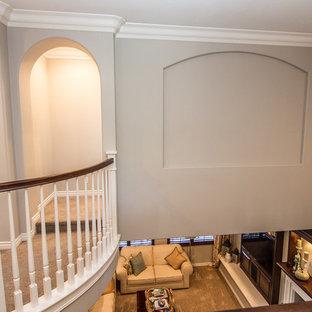 Modelo de dormitorio tipo loft, tradicional renovado, de tamaño medio, con paredes beige, moqueta, chimenea tradicional y marco de chimenea de madera