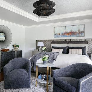Großes Klassisches Hauptschlafzimmer mit grauer Wandfarbe, braunem Holzboden, Kamin, Kaminumrandung aus Backstein, braunem Boden und Tapetendecke in Orange County