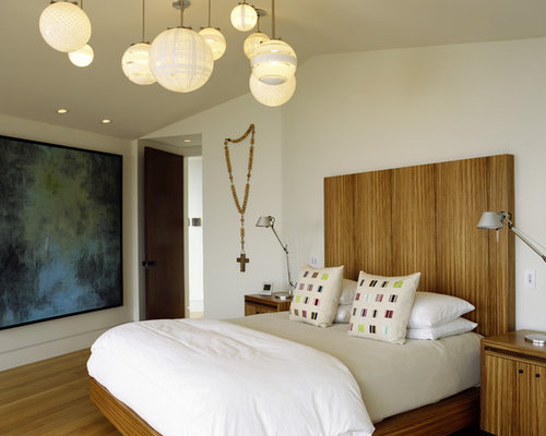 Modern Medium Tone Wood Floor Bedroom Idea In Orange County With Beige Walls