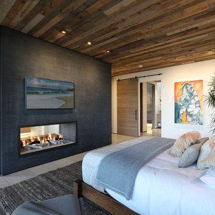 На фото: хозяйская спальня в современном стиле с белыми стенами, двусторонним камином и серым полом с