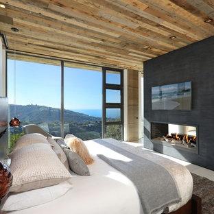 Diseño de dormitorio principal, actual, grande, con paredes beige, suelo de baldosas de porcelana, chimenea de doble cara, marco de chimenea de yeso y suelo beige
