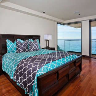 Inspiration for a contemporary dark wood floor and brown floor bedroom remodel in Orange County with white walls