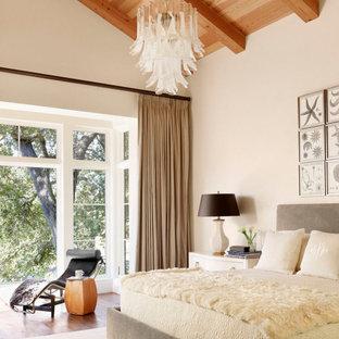 オースティンの中くらいの地中海スタイルのおしゃれな主寝室 (ベージュの壁、無垢フローリング、暖炉なし、茶色い床、表し梁、三角天井、板張り天井) のインテリア