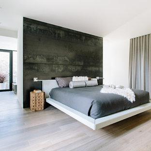 Diseño de dormitorio principal, minimalista, con paredes negras, suelo de madera clara y suelo beige