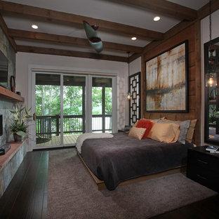 Foto de dormitorio principal, rústico, de tamaño medio, con paredes beige, suelo de madera oscura, chimenea lineal y marco de chimenea de piedra
