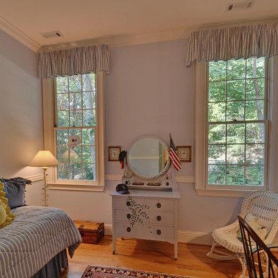 Elegant medium tone wood floor and orange floor bedroom photo in Atlanta with blue walls