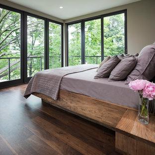 Modelo de dormitorio principal, moderno, pequeño, con paredes beige y suelo de madera en tonos medios
