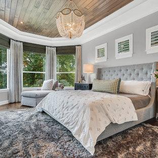 オーランドの大きいトランジショナルスタイルのおしゃれな主寝室 (グレーの壁、無垢フローリング、茶色い床、暖炉なし)