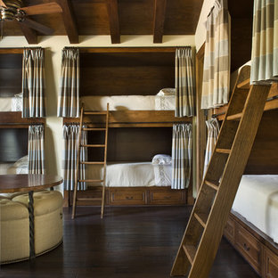 This is an example of a country guest bedroom in Austin with dark hardwood floors.