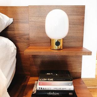 Modelo de dormitorio principal, minimalista, extra grande, con paredes blancas, suelo laminado, chimenea tradicional, marco de chimenea de baldosas y/o azulejos y suelo marrón