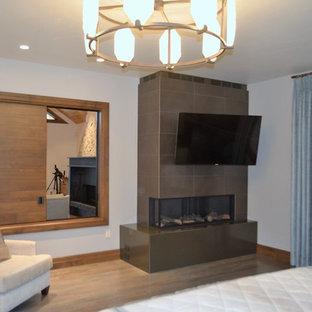 Diseño de dormitorio principal, industrial, de tamaño medio, con paredes beige, suelo de madera en tonos medios, chimenea tradicional, marco de chimenea de baldosas y/o azulejos y suelo marrón