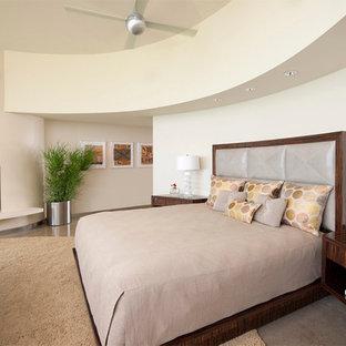 Неиссякаемый источник вдохновения для домашнего уюта: большая хозяйская спальня в стиле ретро с бежевыми стенами, бетонным полом, стандартным камином, фасадом камина из штукатурки и серым полом