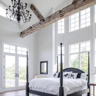 Cette image montre une chambre parentale marine de taille moyenne avec un mur blanc et un sol en bois brun.