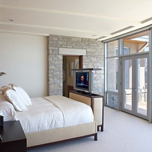 Photo of a modern bedroom in Milwaukee with beige walls and carpet.