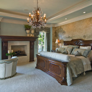 This is an example of a mediterranean bedroom in Charlotte with blue walls, carpet and a standard fireplace.