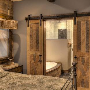Ejemplo de habitación de invitados rústica, de tamaño medio, con paredes azules, suelo de madera en tonos medios y suelo multicolor