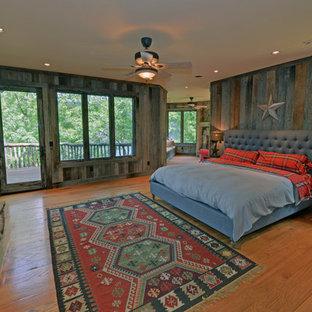アトランタのラスティックスタイルのおしゃれな寝室 (無垢フローリング、標準型暖炉、石材の暖炉まわり)