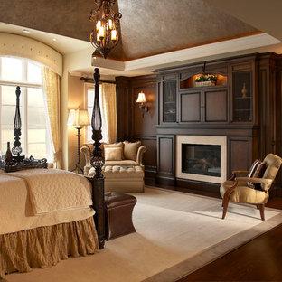 Свежая идея для дизайна: большая хозяйская спальня в классическом стиле с бежевыми стенами, темным паркетным полом, стандартным камином и фасадом камина из дерева - отличное фото интерьера