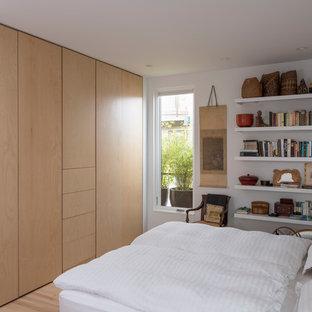 Bild på ett maritimt sovrum, med vita väggar, ljust trägolv och beiget golv