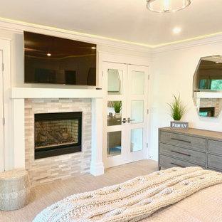 Immagine di una grande camera degli ospiti design con pareti bianche, moquette, camino classico, cornice del camino in pietra ricostruita e pavimento beige