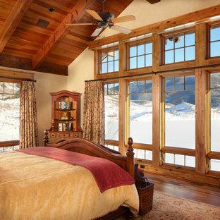 Diseño de dormitorio principal, rural, grande, con paredes beige, suelo de madera oscura y suelo marrón