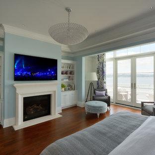 Неиссякаемый источник вдохновения для домашнего уюта: огромная хозяйская спальня в классическом стиле с синими стенами, темным паркетным полом, стандартным камином, фасадом камина из штукатурки и синим полом