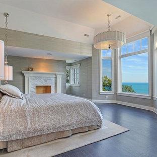 Imagen de dormitorio principal, tradicional, grande, con paredes beige, suelo de baldosas de cerámica, chimenea tradicional y marco de chimenea de piedra