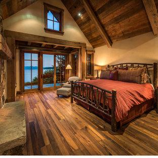 Idee per una grande camera matrimoniale stile americano con pareti beige, pavimento in legno massello medio, cornice del camino in pietra e camino classico