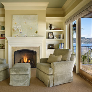 This is an example of a mid-sized mediterranean master bedroom in Seattle with green walls, carpet, a standard fireplace and a stone fireplace surround.