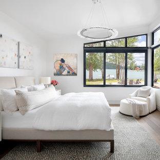 他の地域の中くらいのコンテンポラリースタイルのおしゃれな主寝室 (白い壁、無垢フローリング、横長型暖炉、漆喰の暖炉まわり、茶色い床) のレイアウト