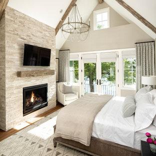 Immagine di una camera matrimoniale chic di medie dimensioni con pareti beige, pavimento in legno massello medio, camino classico, cornice del camino in pietra e pavimento marrone
